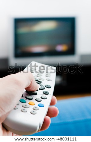 Switching the channels. Hand with remote TV control - stock photo