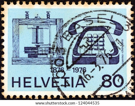 SWITZERLAND - CIRCA 1976: A stamp printed in Switzerland issued for the telephone centenary shows telephones of 1876 and 1976, circa 1976.