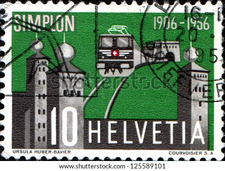 SWITZERLAND - CIRCA 1956: A stamp printed in Switzerland issued for the 50th anniversary of opening of Simplon Tunnel shows electric train emerging from the tunnel and Stockalper Palace, circa 1956 - stock photo