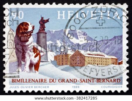 SWITZERLAND - CIRCA 1989: a stamp printed in Switzerland shows St. Bernard Dog, Statue of Saint and Hospice on Summit, Great St. Bernard Pass Bimillennium, circa 1989 - stock photo