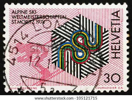SWITZERLAND - CIRCA 1973: a stamp printed in the Switzerland shows Skier and Championship Emblem, International Alpine Skiing Championships, St. Moritz, Switzerland, circa 1973 - stock photo