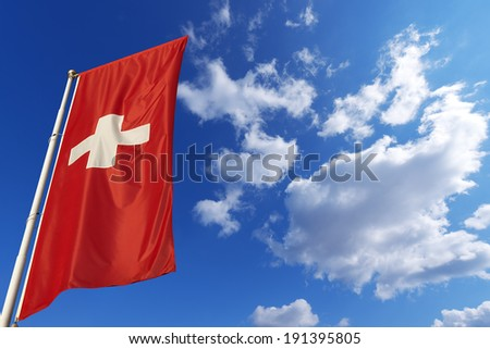 Switzerland Flag in Blue Sky / Flags of Switzerland waving in the wind on blue sky with clouds - stock photo