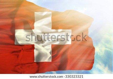 Switzerland waving flag against blue sky with sunrays - stock photo