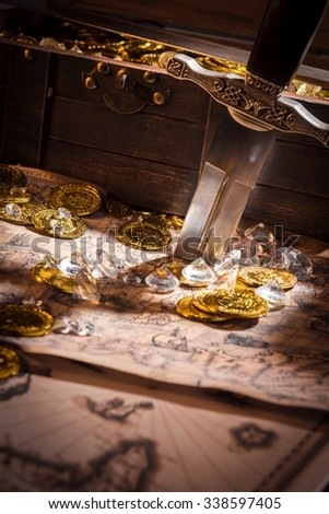 sword, gold coins and diamonds on a map - stock photo