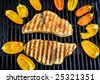 swordfish steaks cook on the bar-b-que grill with baby bell peppers outdoors in a garden - stock photo