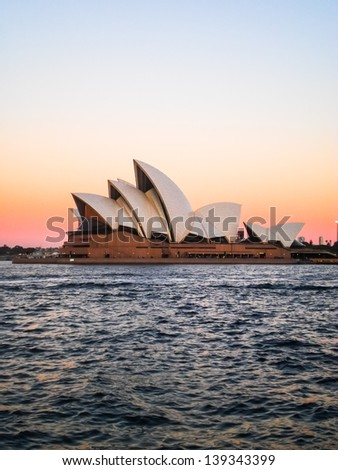 SYDNEY-AUGUST 25 : Sydney opera house with pink sky evening view on 25 August 2011 in Sydney. It was designed by Danish architect Jorn Utzon. - stock photo