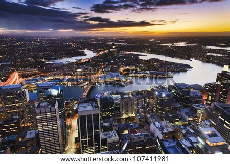 Sydney Australia aerial view from Sydney Tower at sunset with orange sky and clouds at city with illuminated skyscrapers