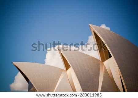 Sydney, Australia - 19 April 2010 : side view of the Sydney Opera House, against a blue sky with some white clouds - stock photo