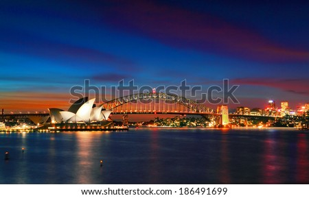 SYDNEY, AUSTRALIA - APRIL 8, 2014; Two of Sydney's famous icons, the Sydney Opera House and Sydney Harbour Bridge lit up at dusk after a vivid sunset, the sky still aglow with colour.   Long exposure - stock photo
