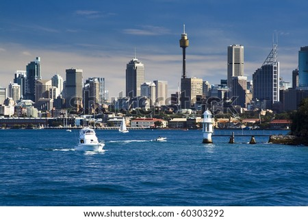 sydney australia CBD close-up with lighthouse and boat in harbour water blue sky skyscrapers - stock photo