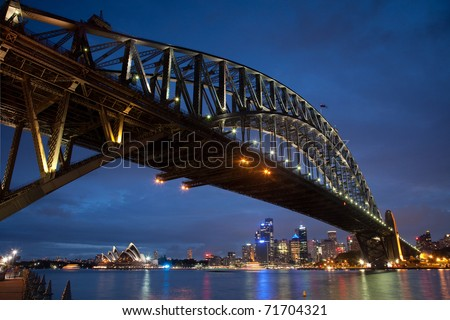 Sydney Australia CBD view from under Harbour bridge side view on City and opera illuminated at sunset