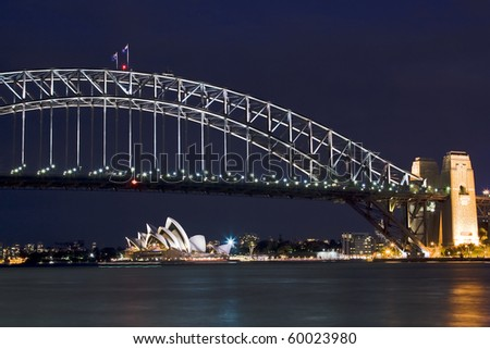 sydney australia harbour bridge opera house night scene highlighted illuminatoin by lights blue sky - stock photo