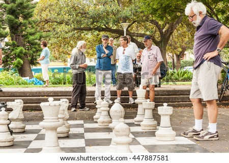 SYDNEY, AUSTRALIA - JANUARY 29; Group of men looking on in park in quiet contemplation while an outdoor game of chess is being played January 29, 2011, Sydney Australia.