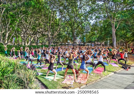 SYDNEY, AUSTRALIA-JANUARY 9, 2015 : People enjoy in free classes joga at Hyde park for Sydney festival in Sydney, Australia on January 9,2015. Sydney festival start about January every year . - stock photo