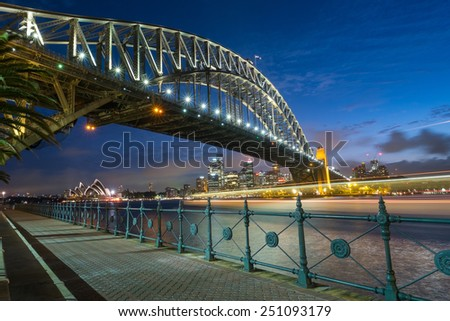 SYDNEY, AUSTRALIA- JANUARY 5, 2015: The iconic Sydney Harbour Bridge with Sydney Opera House in the background at dusk on a January evening, 2015 - stock photo