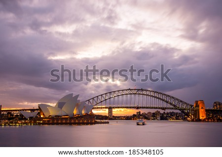 Sydney, Australia - July 11, 2010 : Dramatic sky and the Sydney Opera House at dusk. Sydney skyline taken from Mrs. Macquarie's Point. - stock photo