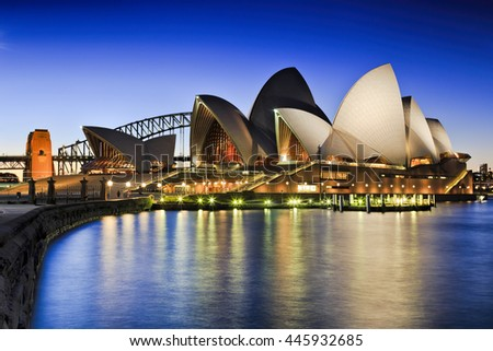SYDNEY, AUSTRALIA, 1 JULY 2016 - Sydney opera house and Harbour bridge  at sunset reflecting illumination lights in blurred cove waters as seen from Royal Botanic Garden.