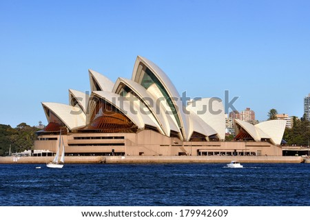 SYDNEY, AUSTRALIA - JULY 03, 2011: Sydney Opera House basking in the sun on a perfect Winter's day. In the foreground is the harbour, a yacht and motor boat. - stock photo