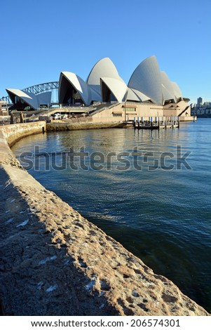 Sydney, Australia - July 17, 2014: Sydney Opera House vertical view with wall in foreground on a winter morning. - stock photo