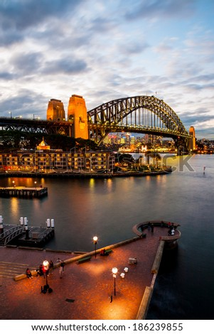 Sydney, Australia - July 12, 2010 : Urban Scene of Sydney Harbour with the Harbour Bridge at dusk. Travelers are enjoying the night view of Sydney. - stock photo