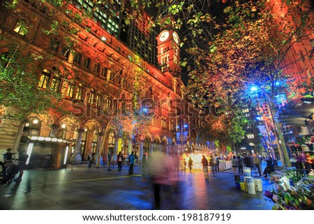 SYDNEY, AUSTRALIA - JUNE 6, 2014;   Martin Place, A CBD and shopping district of Sydney lit  in various ever changing colour, during annual Vivid festival.  People in motion.  Sky flower in distance. - stock photo