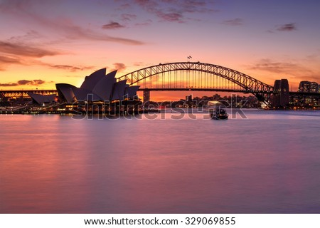 SYDNEY, AUSTRALIA - MAY 25, 2015; Rich vibrant sunset over Sydney with Sydney Harbour Bridge and Opera House also in view..  Boats on the harbour are in motion. - stock photo