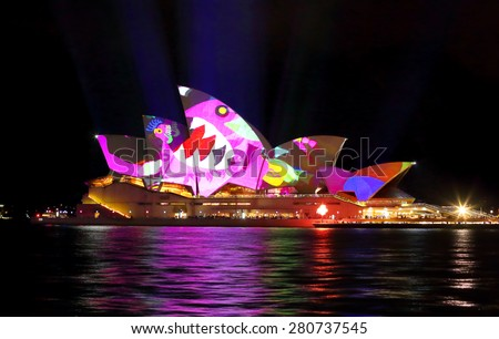 SYDNEY, AUSTRALIA - MAY 22, 2015; Sydney Opera House illuminated with a hungry shark chasing chickens imagery during the Vivid Sydney 2015 annual public event. - stock photo