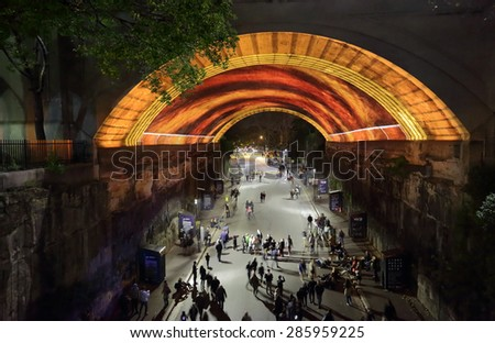 SYDNEY, AUSTRALIA - MAY 23, 2015;  View down into Argyle Street The Rocks as public watch, photograph or video  Life Story  for Vivid Sydney. People in motion - stock photo