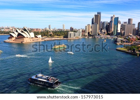 SYDNEY, AUSTRALIA - October 6, 2013:  Sydney Harbour, Circular Quay, City of Sydney and Opera House. Shadow of Sydney Harbour Bridge is reflected in water. - stock photo