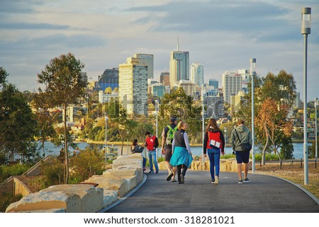 SYDNEY,AUSTRALIA - SEPTEMBER 19,2015: Adults walking together and talking in the newly-created Barangaroo Reserve. It stands on one of Sydney's oldest industrial sites. - stock photo