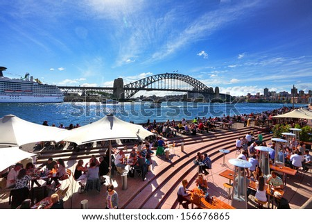 SYDNEY AUSTRALIA - SEPTEMBER 15, 2013: Residents and visitors dine, relax and basque in the glorious afternoon sun quayside by the harbour, Sydney Australia.   - stock photo