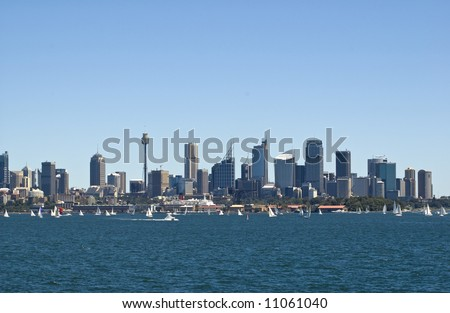 sydney australia skyline from harbor with sailboats in foreground and large expanse of blue sky