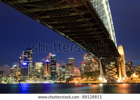 Sydney Australia view on CBD from under harbour bridge giant still arch close-up at dusk time with illuminated skyscrapers - stock photo