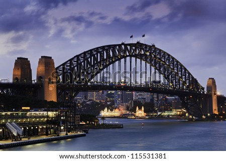 sydney bridge side view from city at sunset with blurred clouds and illuminated lighs - stock photo