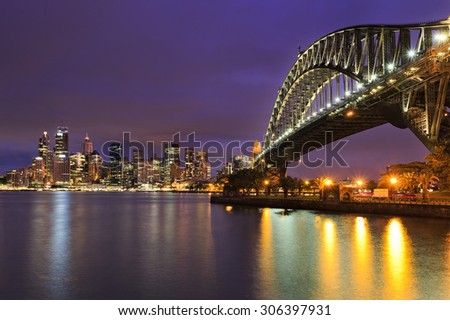 Sydney CBD cityline of illuminated high-rise buildings and harbour bridge with colourful reflection in blurred harbour waters at sunset
