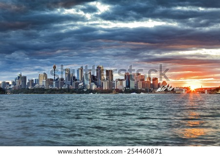 Sydney CBD distant view across Harbour at sunrise with bright sun setting behind city landmarks - stock photo