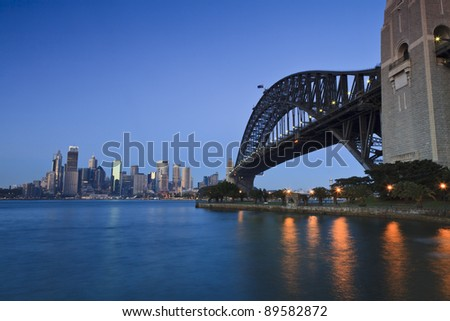 sydney city at sunrise soft light skyscraper reflection and lights in harbour water with arch of the bridge