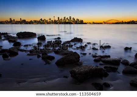 sydney city CBD and harbour bridge sunset view at low tide with sea floor foreground and lights reflection - stock photo