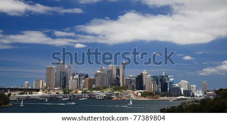 sydney city cbd capital australia cityskape with skyscrapers under blue cloudy sky sunny summer day blue water and boats - stock photo