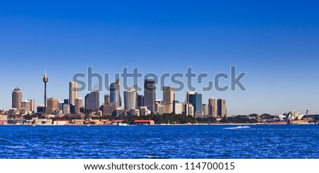 Sydney city CBD cityscape cityline panoramic view from sydney harbour sunny day water and blue sky - major australia landmarks - stock photo