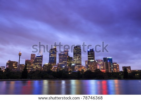 Sydney city CBD cityscape sunset twilight skyscrapers illuminated lights with reflection in harbour water - stock photo