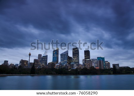 sydney city CBD skyscrapers view over harbour twilight time with heavy cloudy overcast illuminated windows of cityscape - stock photo