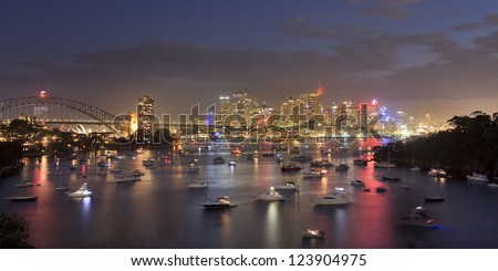 sydney city CBD view from Waverton at sunset with illuminated downtown lights reflect in harbour water crowded with heaps of yachts and boats - stock photo