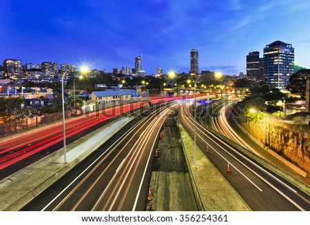 Sydney city domain suburb at sunset view above cross-city toll road motorway when car headligths are blurred and buildings are illuminated - stock photo