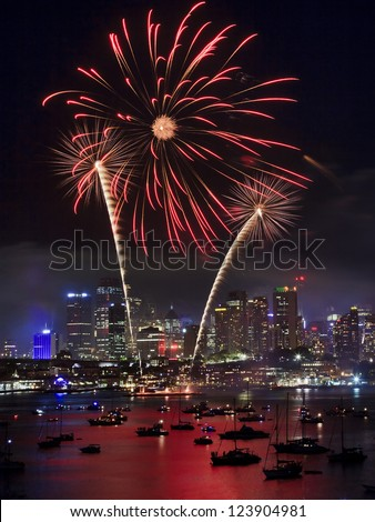 Sydney city firework New year eve illumination and reflection of lights in sydney harbour with boats fire palm tree in the sky vertical