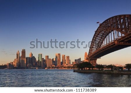 Sydney city harbour and bridge cityscape panoramic view at sunrise with warm sun light blue and pink sky - stock photo