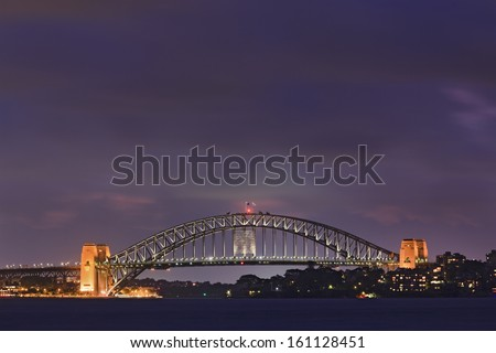 Sydney city Harbour bridge side view at sunset illuminated with lights cloudy dark sky panoramic side view  - stock photo