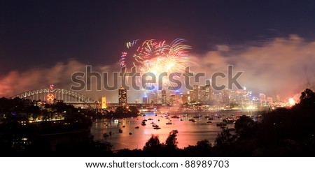 Sydney City panoramic view on fireworks at new year celebration light show dusk lights reflection in harbour over CBD and bridge - stock photo