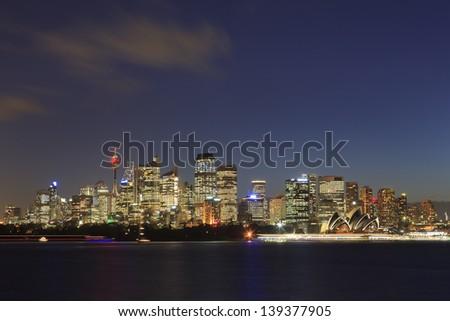 Sydney cityscape at sunset illuminated skyscrapers australia landmark over harbour water - stock photo