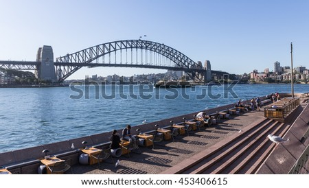 Sydney - February 25, 2016: The flags are developed over the Sydney Harbour Bridge and tourists relax on the waterfront near the Sydney Opera House February 25, 2016, Sydney, Australia
